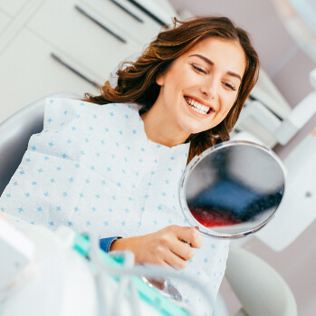 happy woman examining her teeth in a mirror at the dentist's office