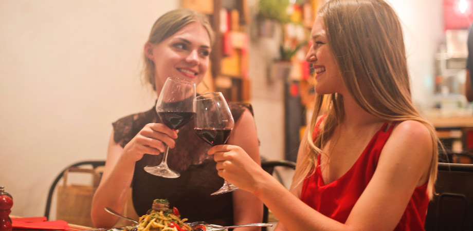two women smiling at each other toasting with glasses of red wine